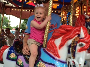 Emma rides the plastic ponies with the steadying hand of her dad.