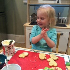 Emmas is eminently pleased with the results of her first try at icing cookies.